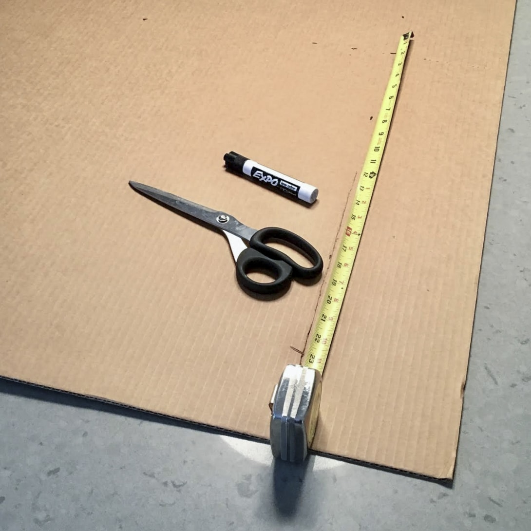 Flat cardboard with tape measure, scissors, and expo marker laying on top