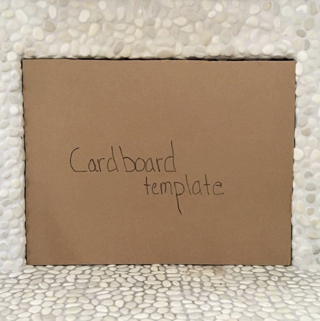 Square cardboard cutout inside of a fireplace opening with the words 'Cardboard template' written on it