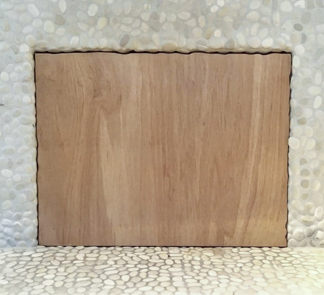 Square piece of plywood sitting as a fireplace insert to block draft