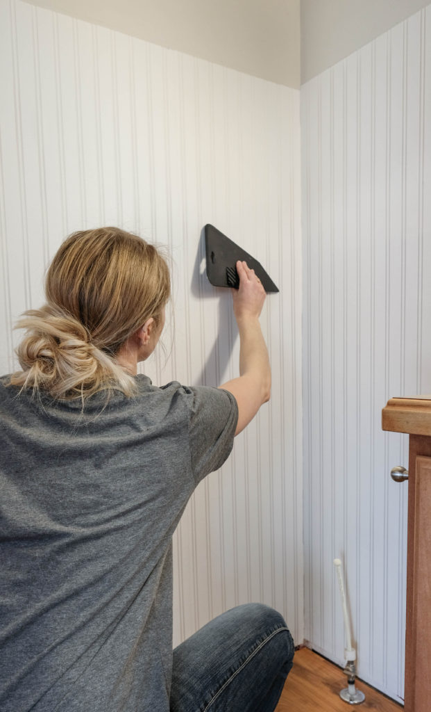 A woman using a wallpaper smoothing tool to smooth beadboard wallpaper onto a wall
