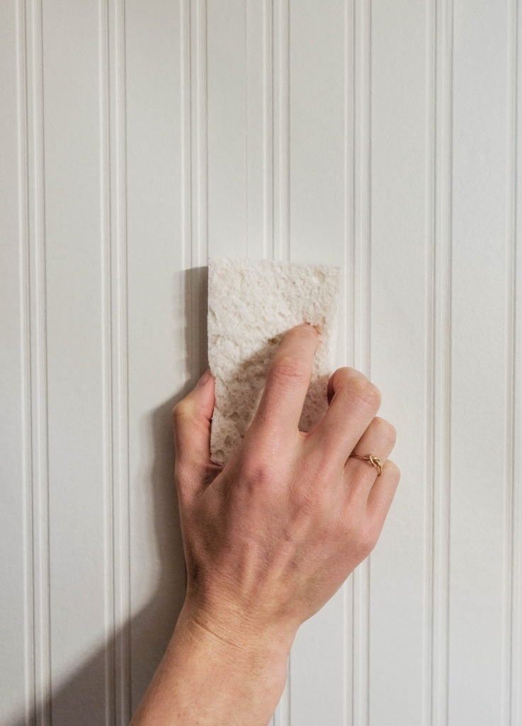 Closeup of a hand holding a sponge against beadboard wallpaper