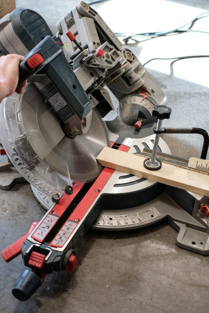 "Miter saw cutting a 1"" x 3"" pine board at a 45 degree angle"