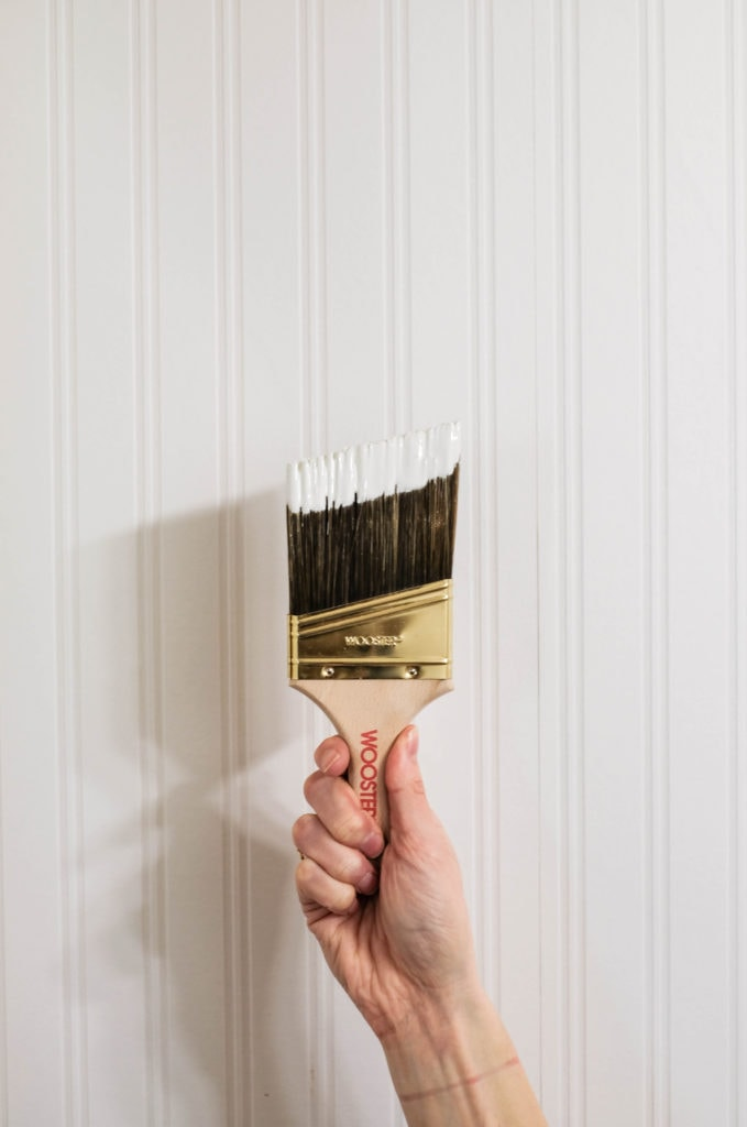 An angled paint brush dipped in white paint being held in front of white beadboad wallpaper