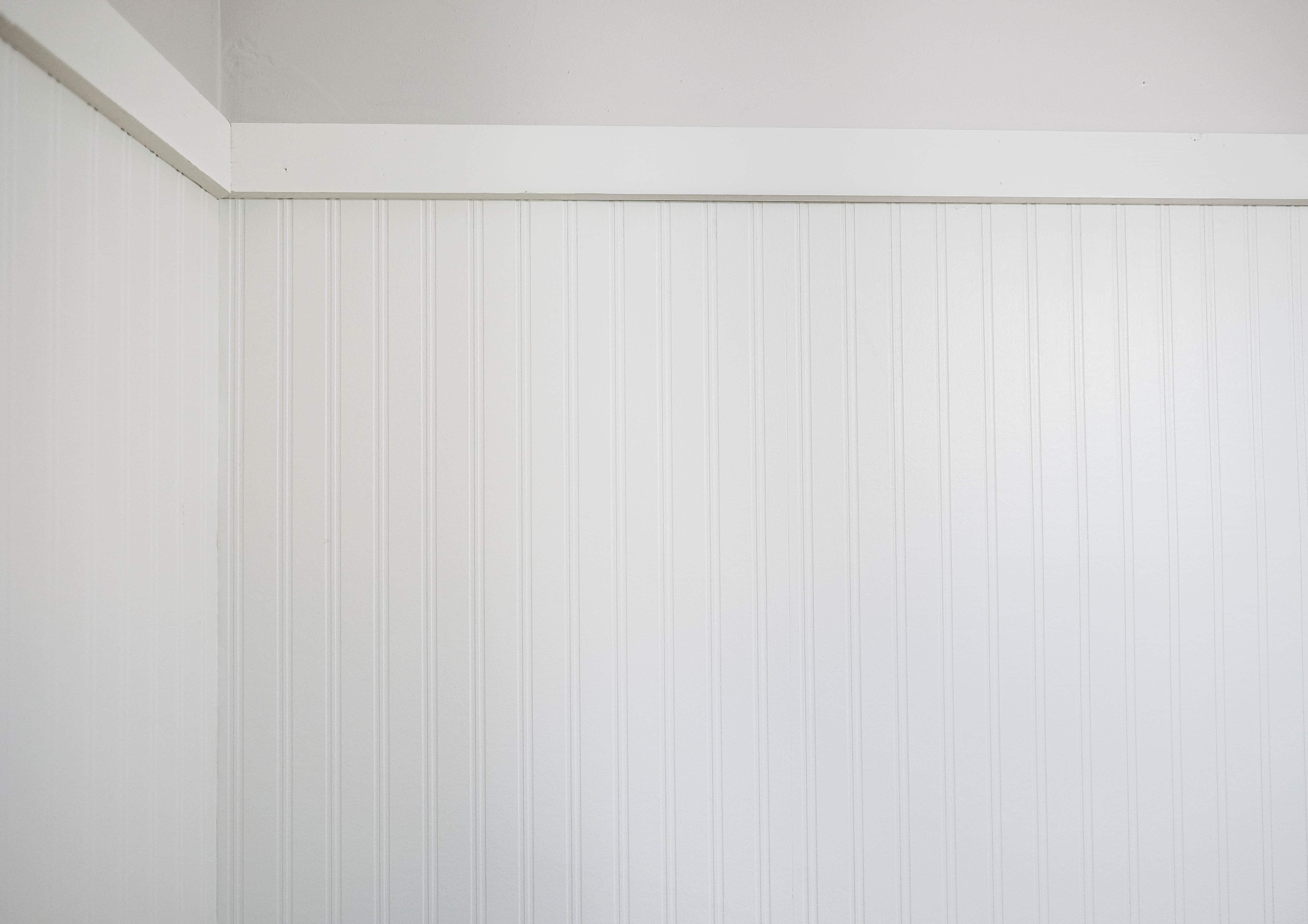 White beadboard wallpaper against light grey wall