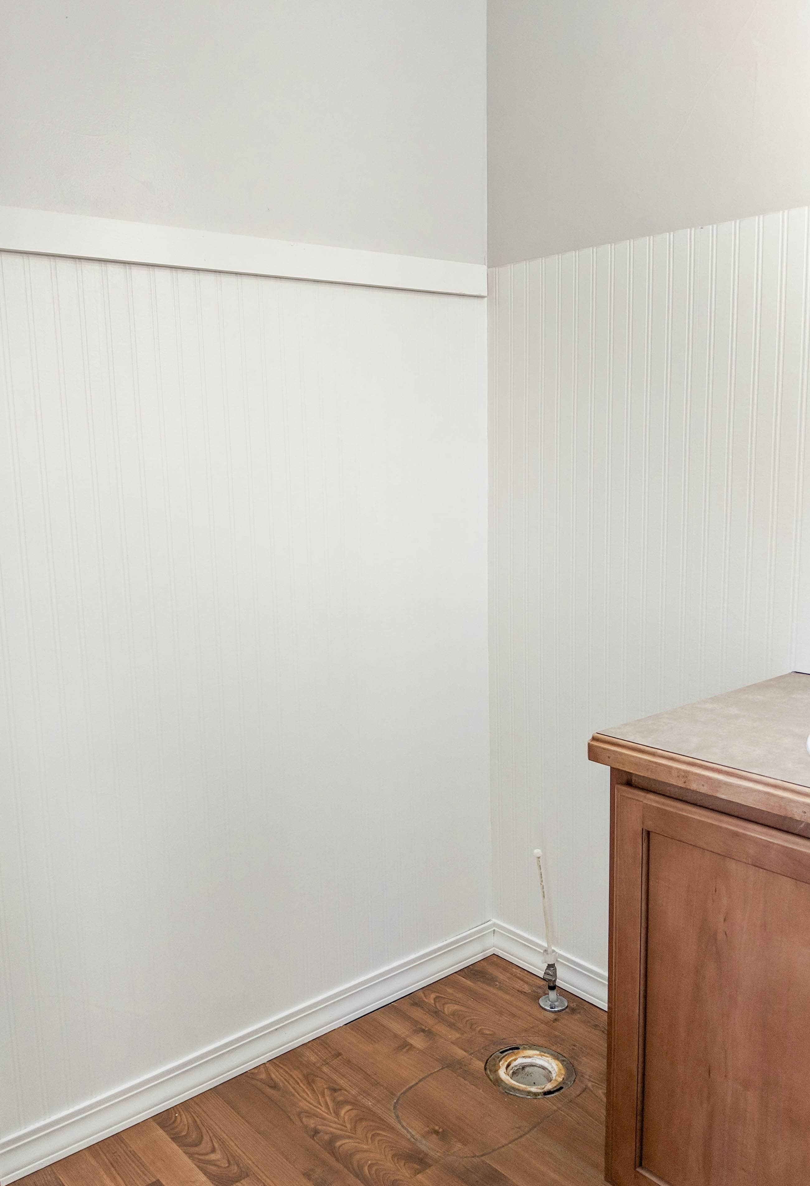Corner of a small bathroom with toilet removed featuring white beadboard wallpaper