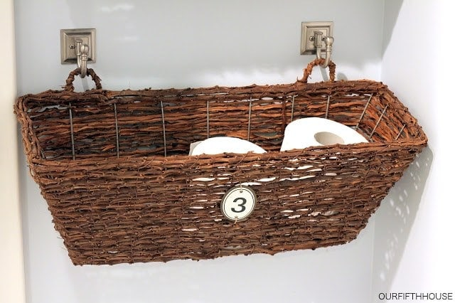 Wicker basket with bathroom items in it hanging from two hooks on the wall