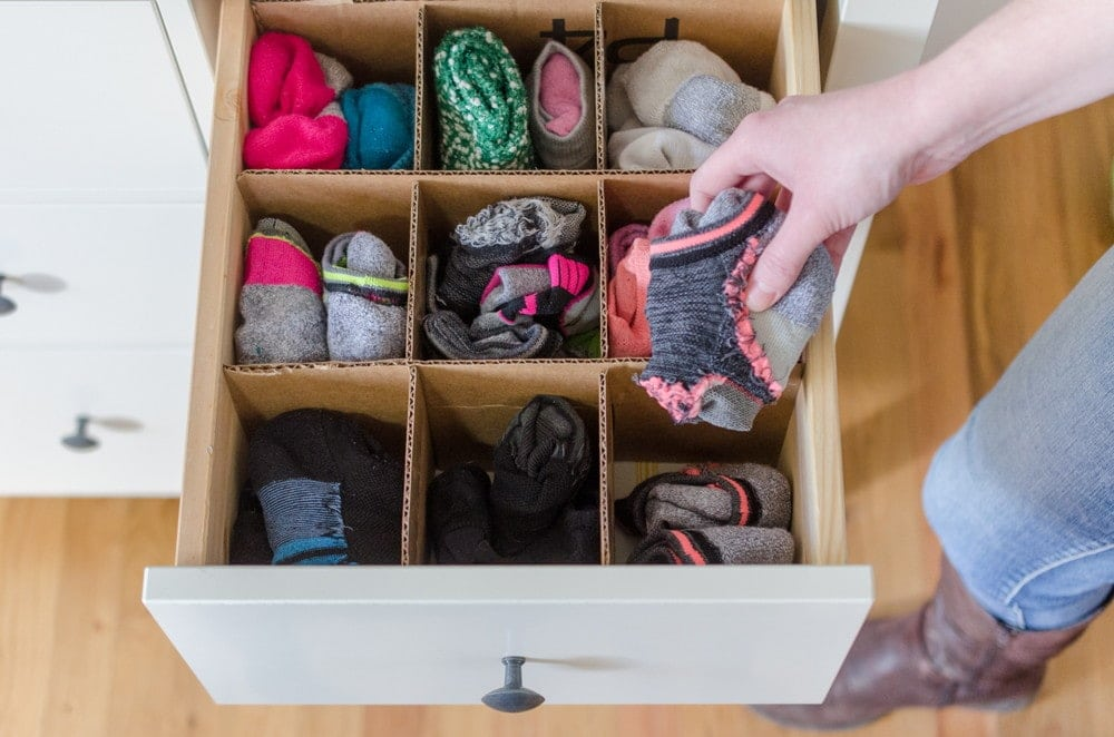 Cardboard cut into strips and placed in a grid pattern being used as sock organization in a drawer