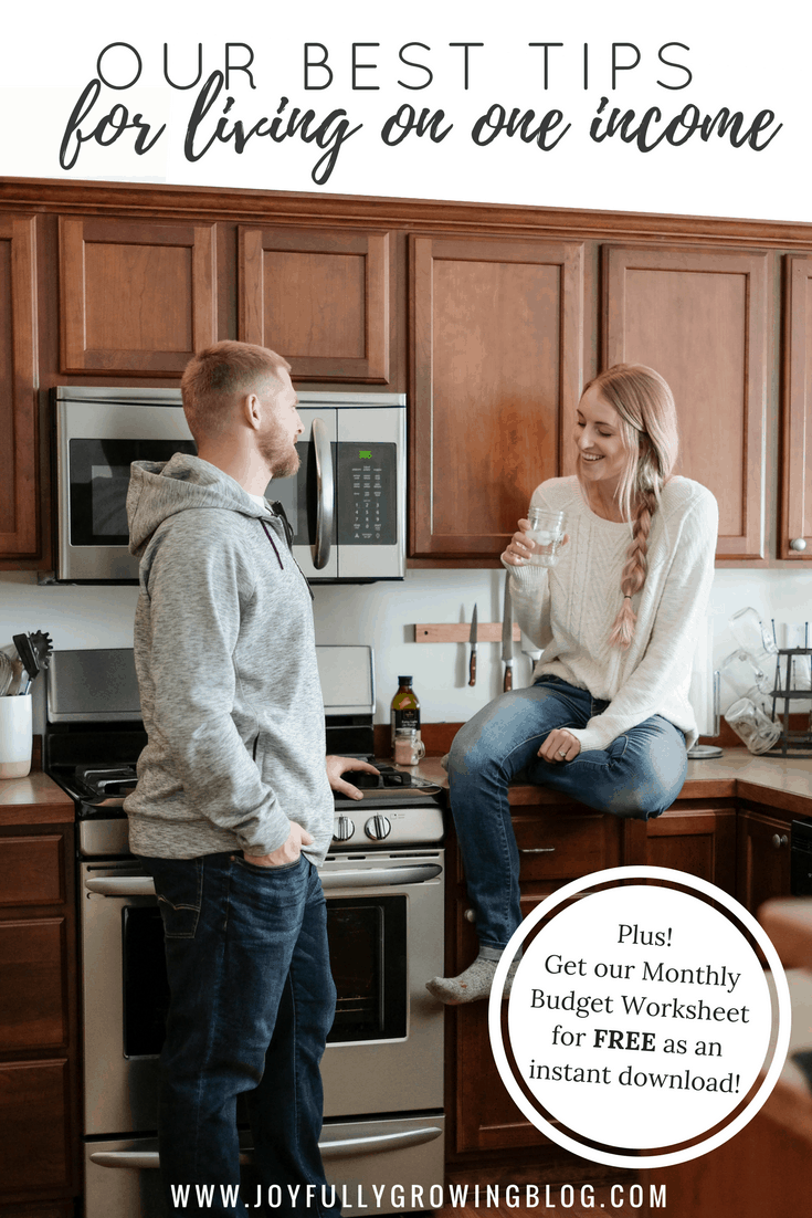 "Two people in the kitchen, one sitting on the counter talking about their budget. Text overlay reads ""Our Best Tips for living on one income"""