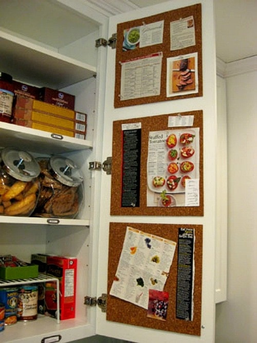 Open kitchen cabinet with cork boards glued to the inside of the door with recipes and sticky notes pinned to the board