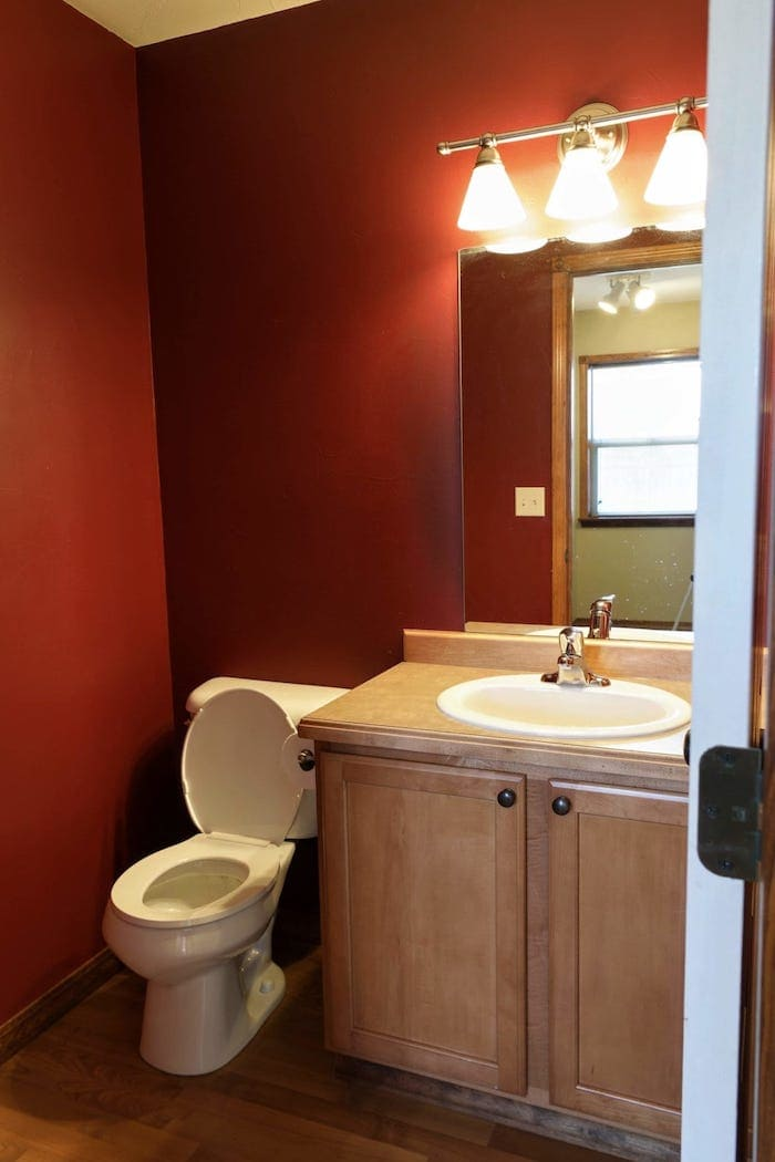bathroom with red walls and builder grade vanity - before