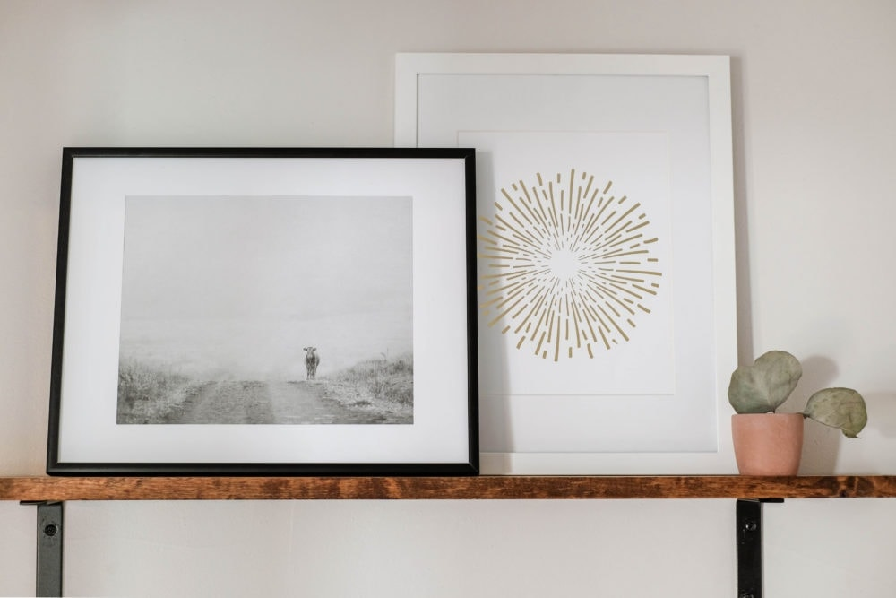 bathroom shelf styled with a framed black and white cow print, and a decorative firework print