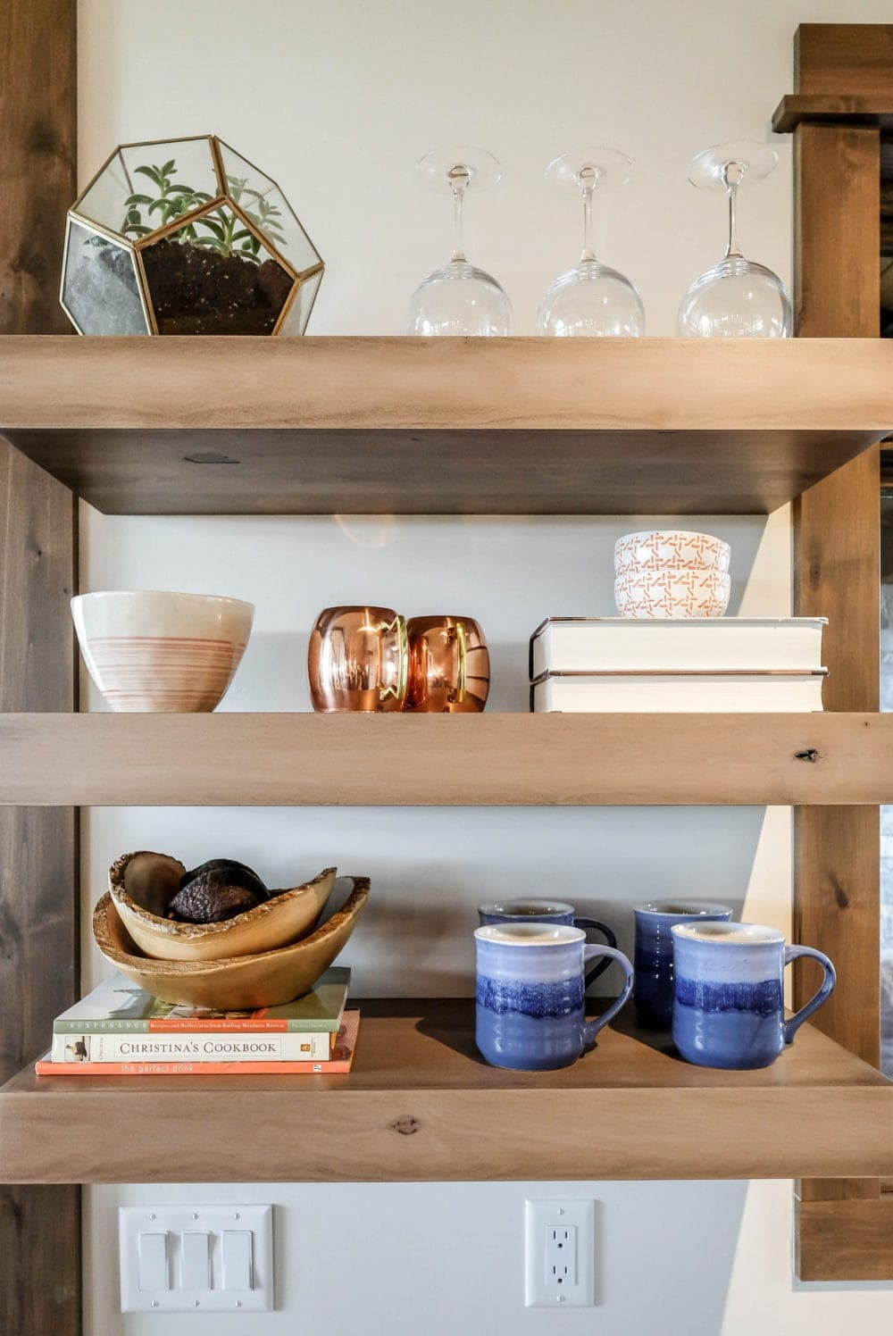 kitchen shelves styled with wine glasses, a bowl, books, and mugs
