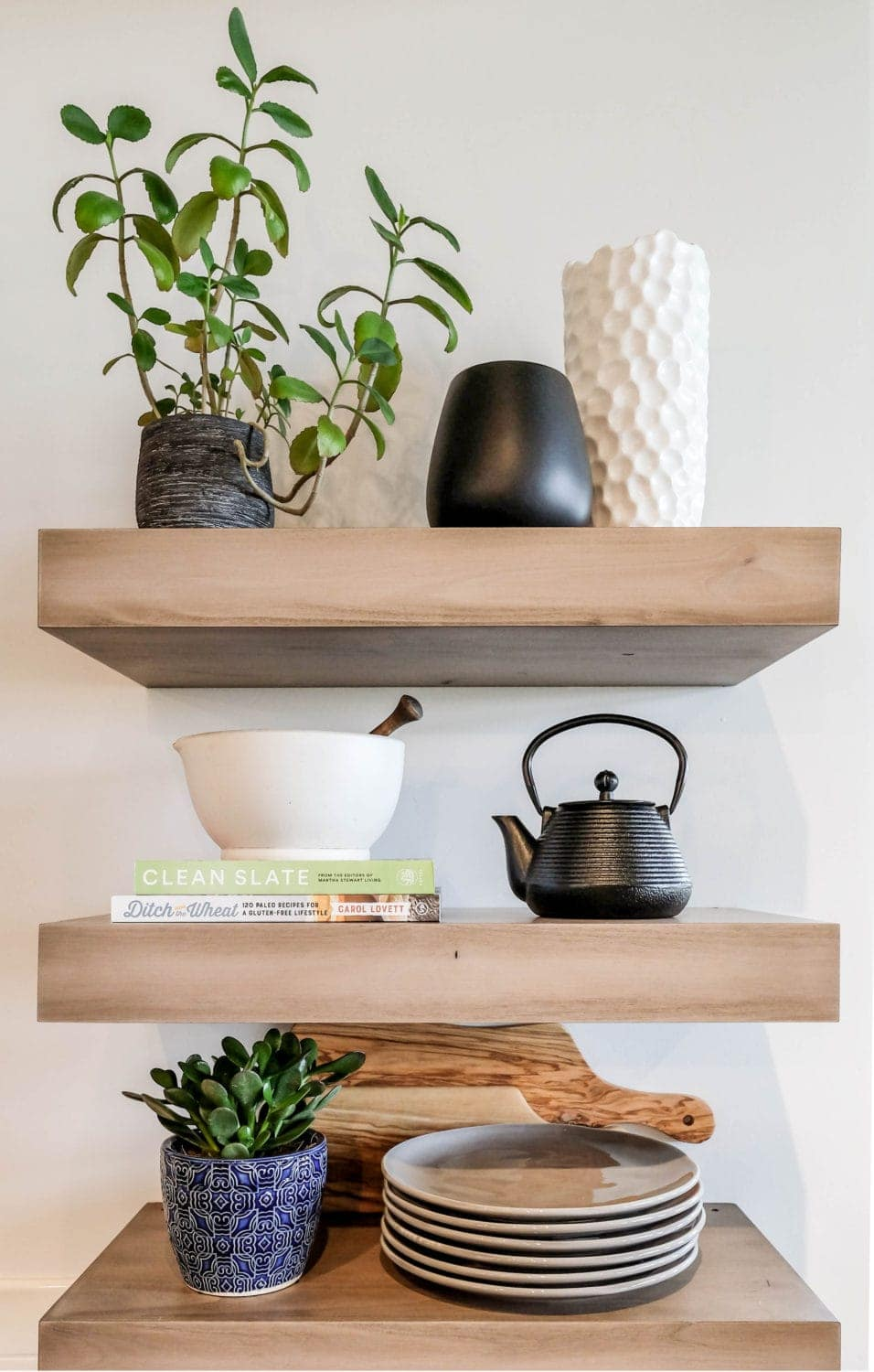 kitchen shelves styled with potted greenery, plates, a kettle, and books