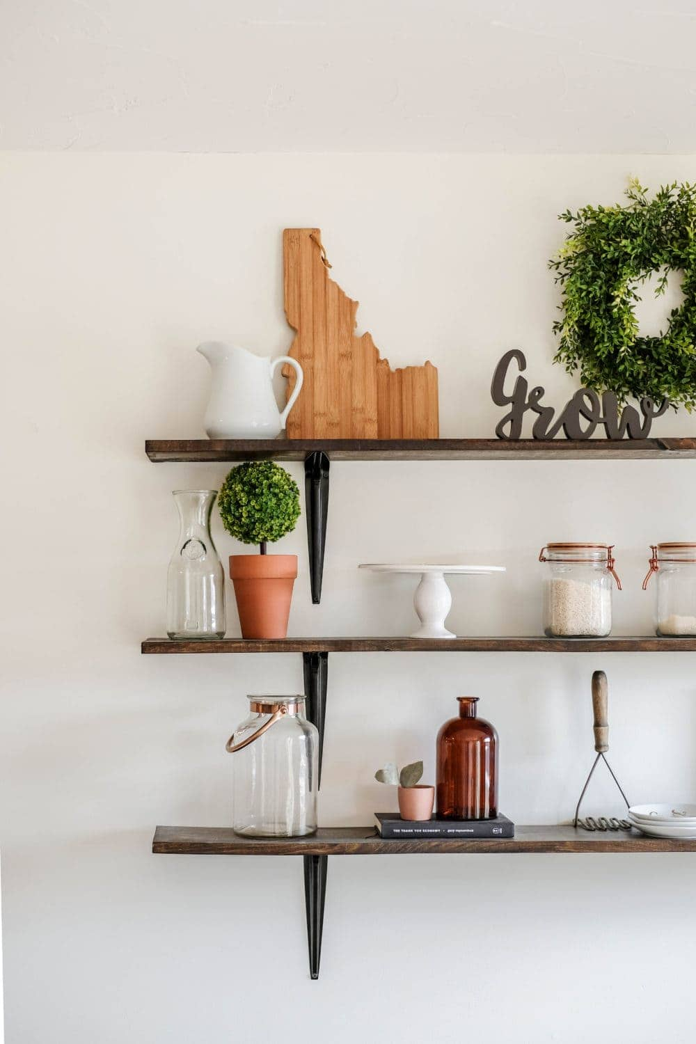 dining room shelves styled with a cutting board, a cake stand, potted greenery and glass canisters