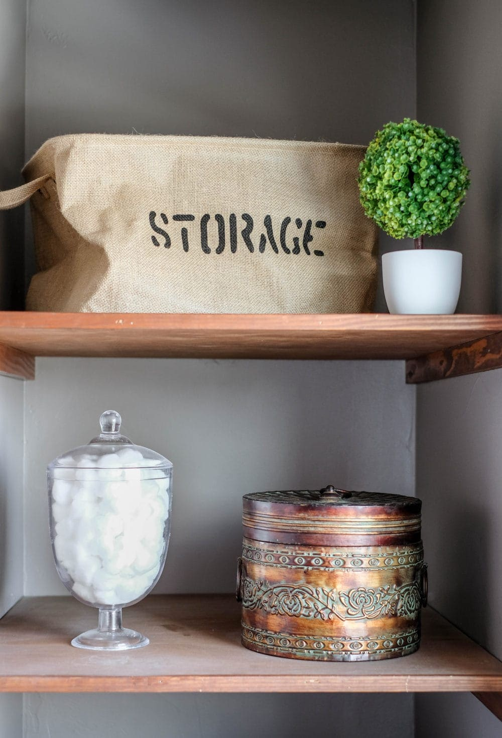 bathroom linens shelves styled with burlap, greenery, and a glass jar for cotton balls