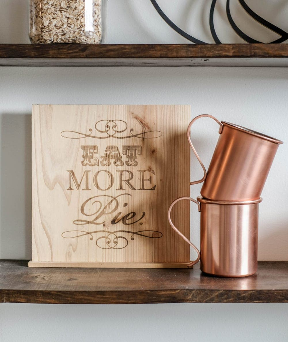 shelf styled with a Eat More Pie sign, and two stacked copper mugs