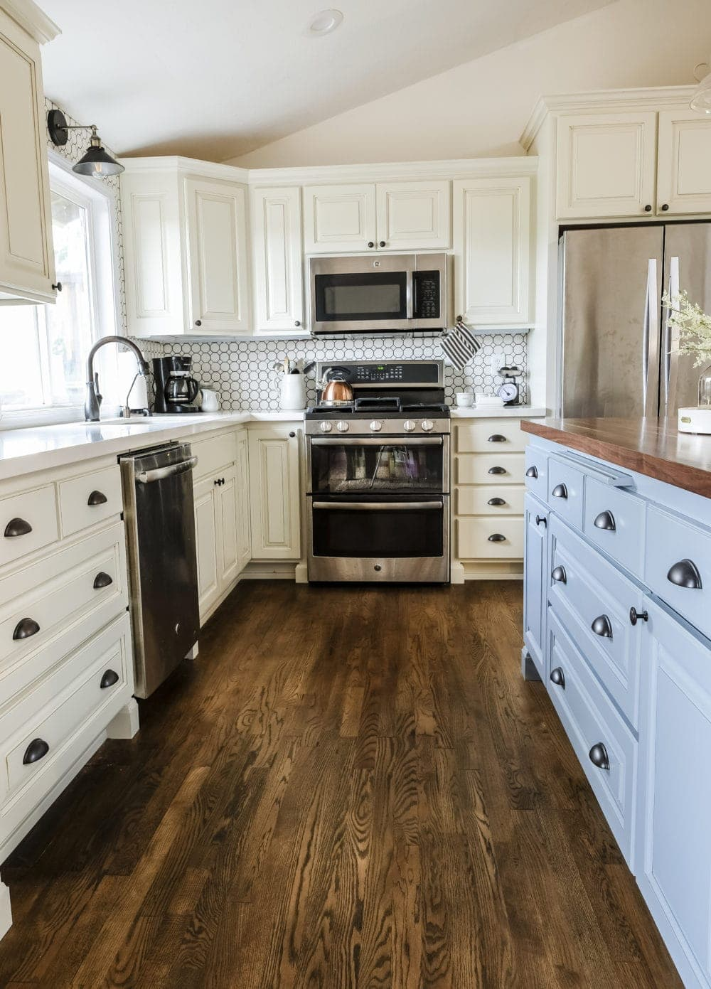 Kitchen with white cabinets and a blue kitchen island with farmhouse finshes and hardwood floors