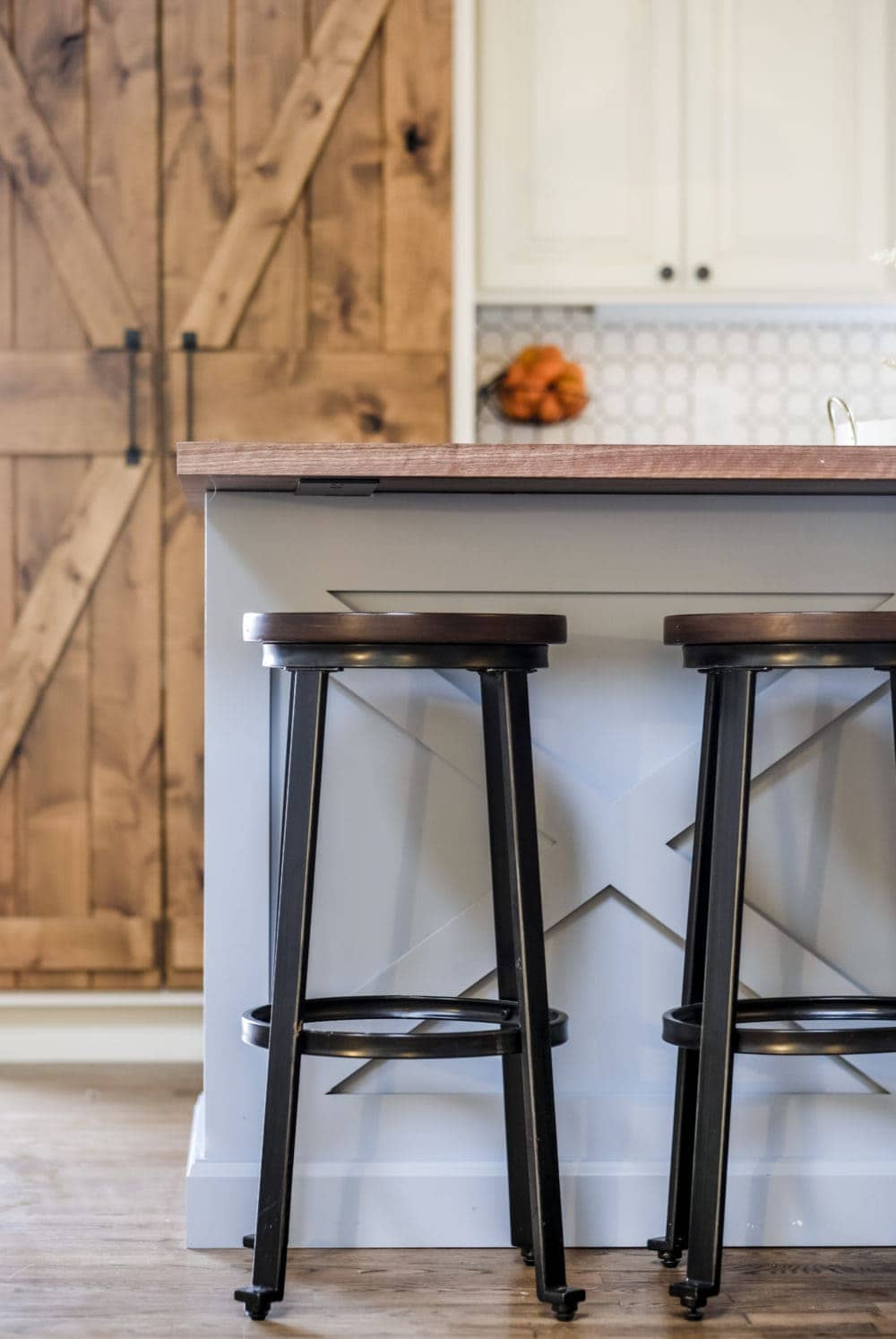 Rustic bar stools in front of a blue kitchen island