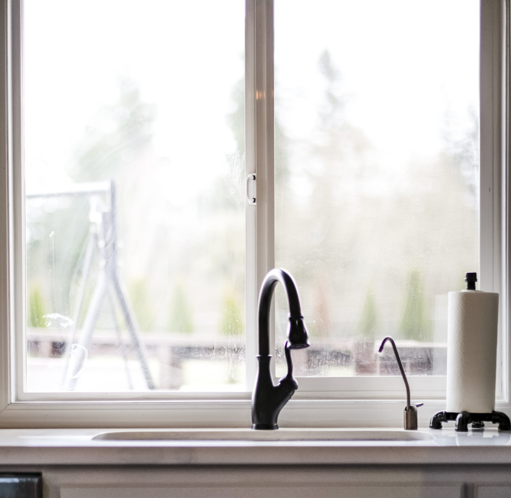Kitchen sink with oil rubbed faucet in front of a large window