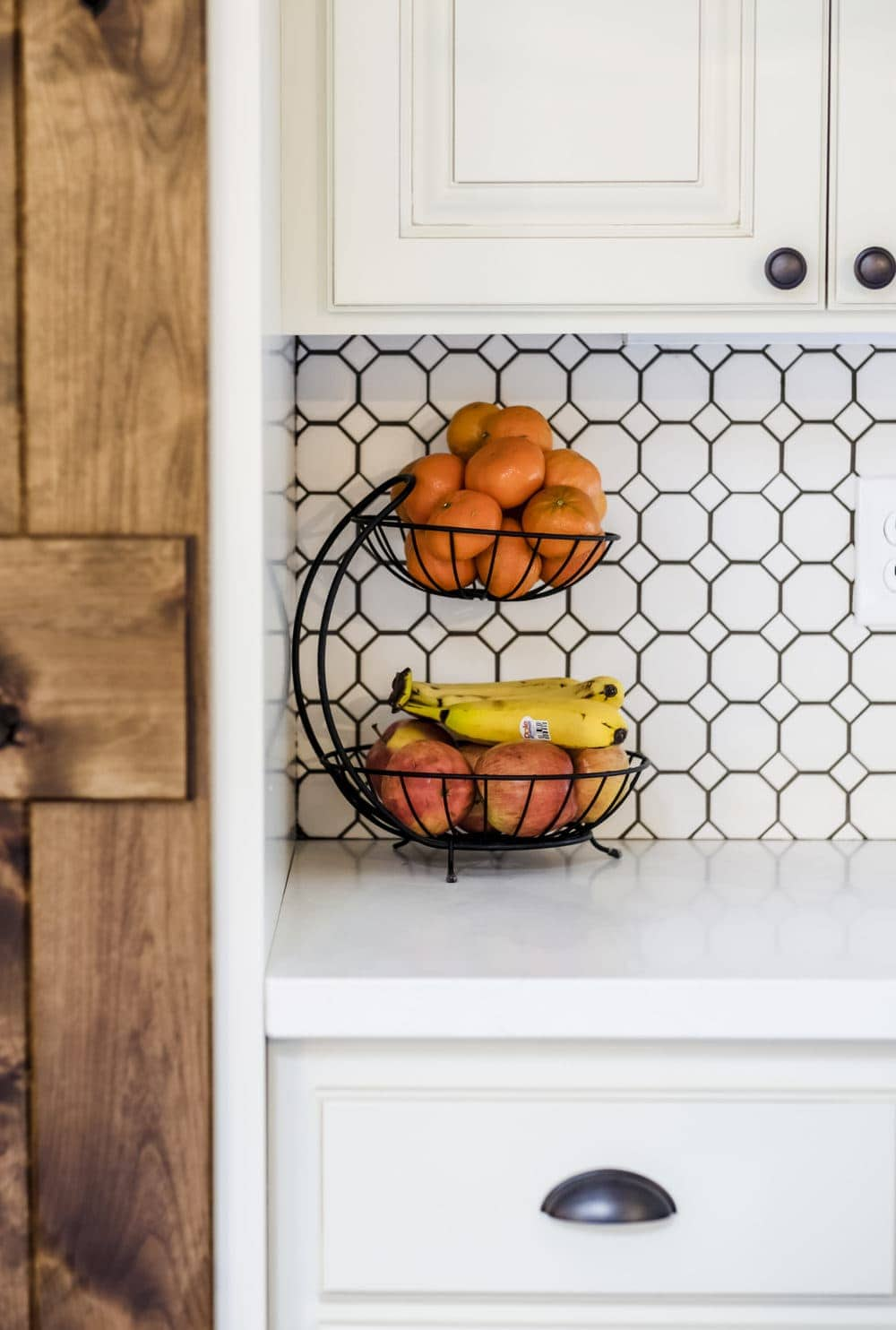 Black stacked fruit basket with oranges and bananas against white penny tile backsplash