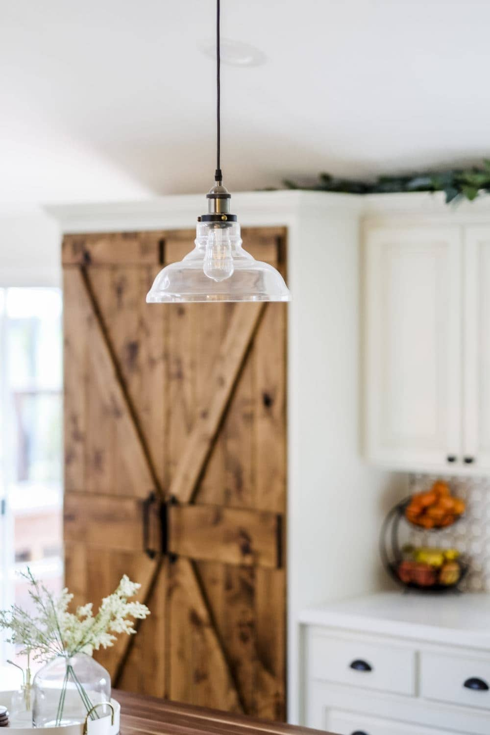 Glass pendant light hanging in white farmhouse kitchen on a budget