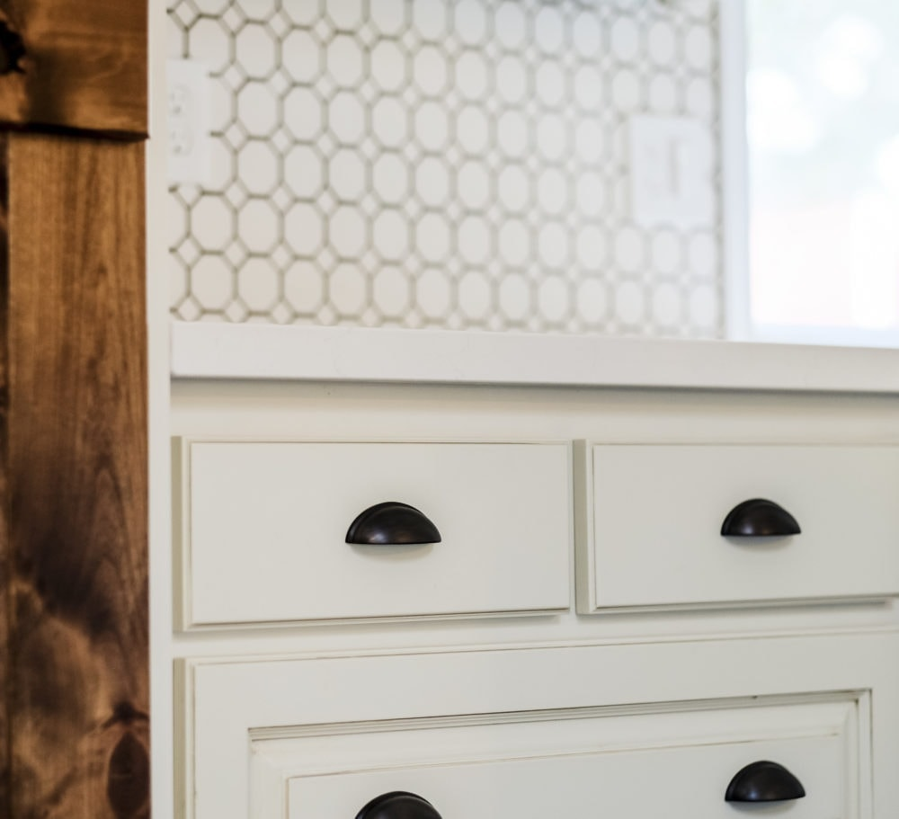 Closeup of oil rubbed bronze cabinet hardware one white drawers for a kitchen on a budget