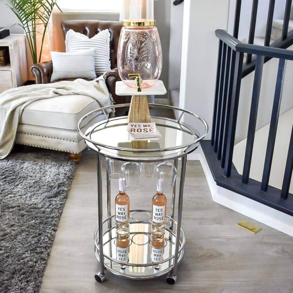 Summer bar cart with empty drink dispenser and hanging wine glasses