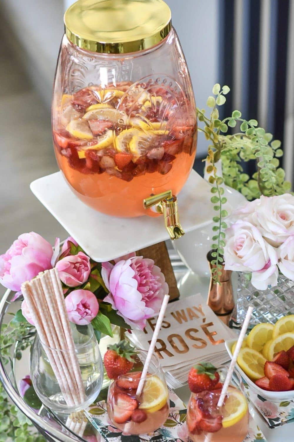 Summer bar cart decorated with flowers and a large drink dispenser with strawberry lemonade sangria