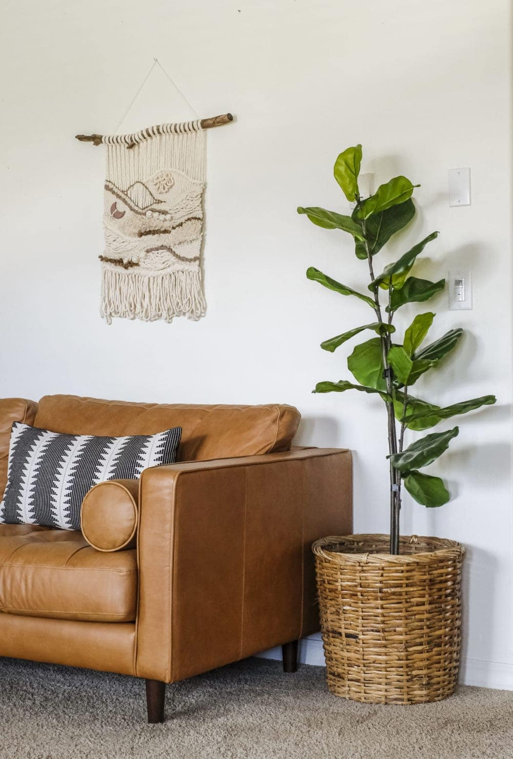 faux fiddle leaf fig tree in a woven basket sitting in a living room