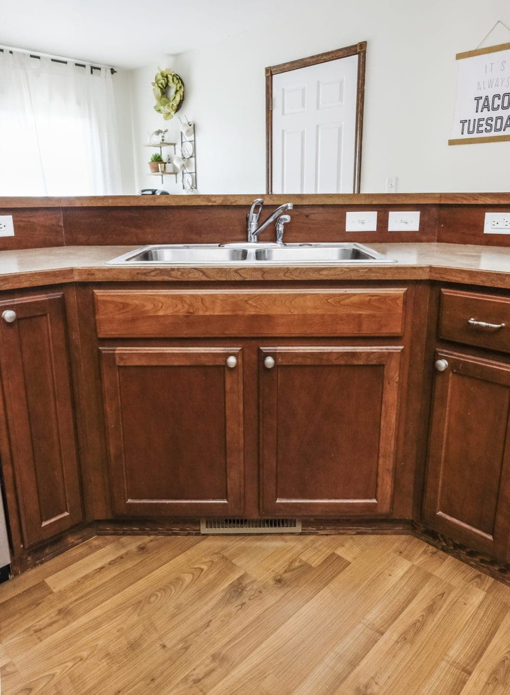 A stainless steel builder grade sink with dark wood cabinets