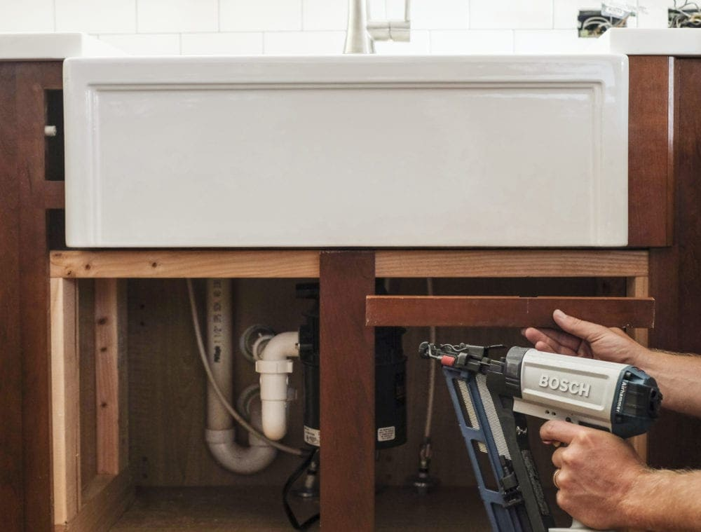 Nail gun installing cabinet trim piece under farmhouse sink