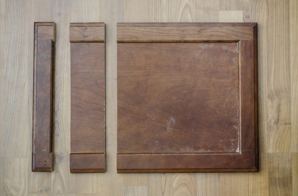 Cabinet door on ground with 2 cuts creating a middle piece to be removed