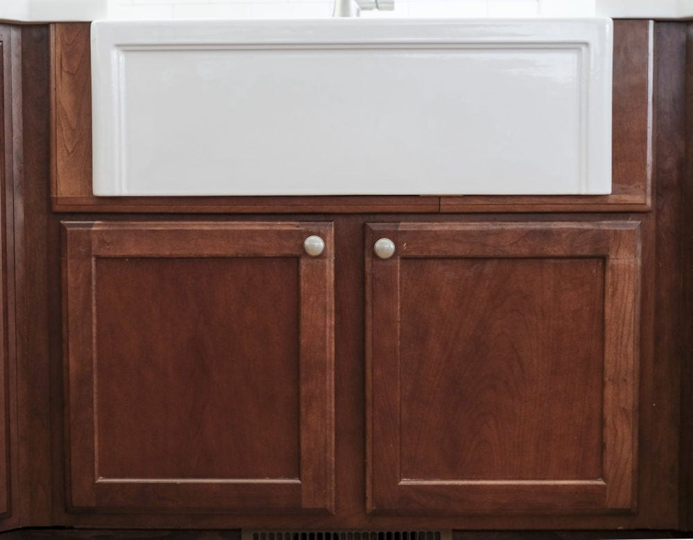 View of white farmhouse sink with custom built cabinet doors below