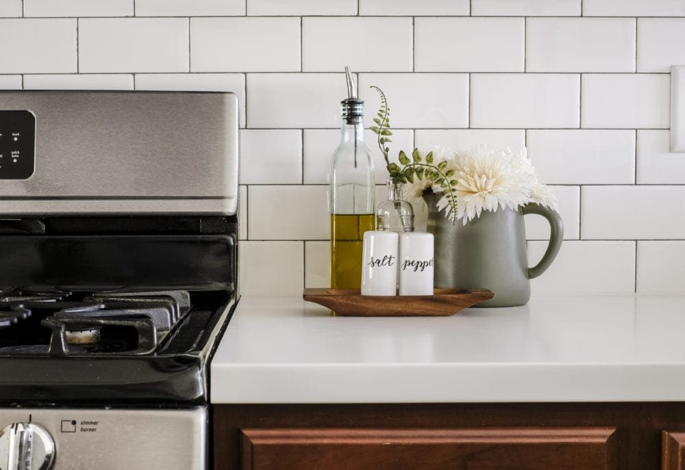 white countertops and subway tile decorated with salt and pepper shakers and olive oil dispenser