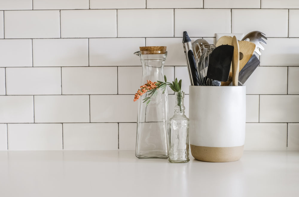 kitchen cooking utensils on white counter tops with white subway tile backsplash