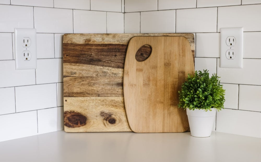 wood cutting boards leaned against white subway tile back splash