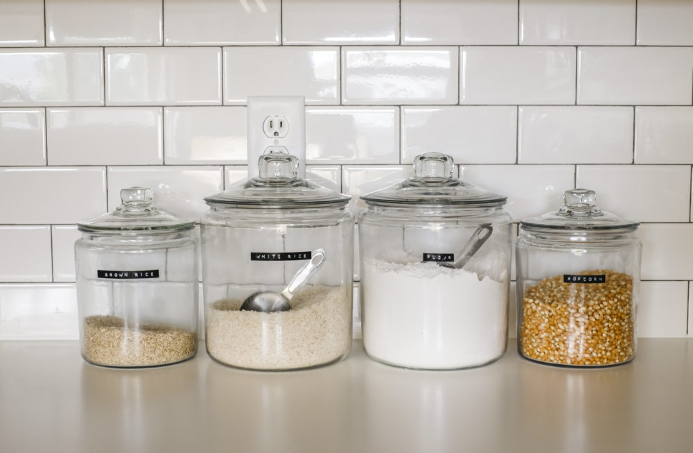 rice, flour, and popcorn jars on a white counter top with a white subway tile back splash
