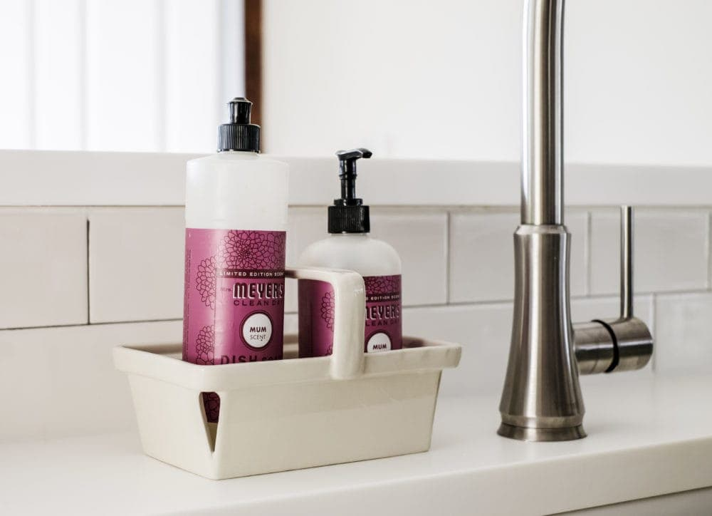Meyers soap sitting on white solid surface counter tops in front of a subway tile backsplash