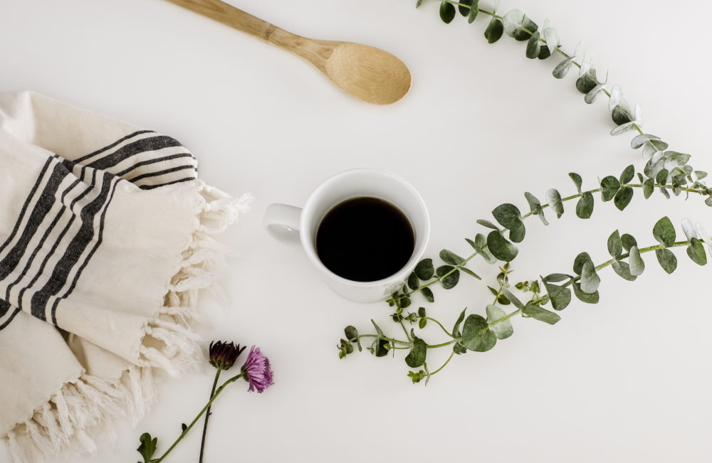white solid surface countertops with a cup of coffee, a dishtowel and eucalyptus leaves