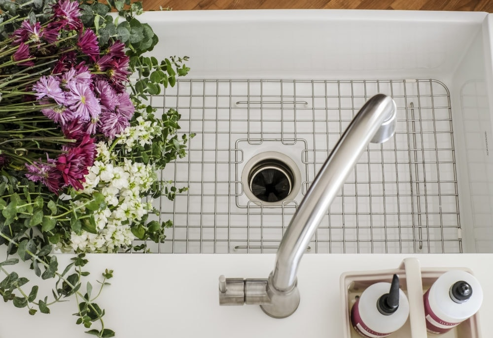 white sinkology farmhouse sink with metal grate in the bottom decorated with fresh flowers