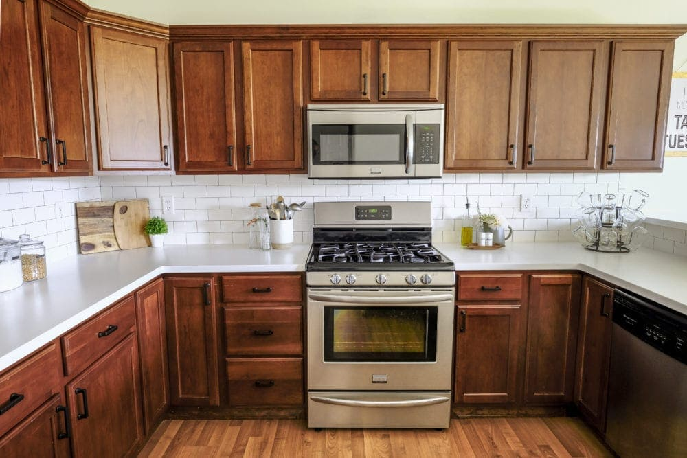 kitchen after remodel with wood cabinets, white countertops and subway tile backslash