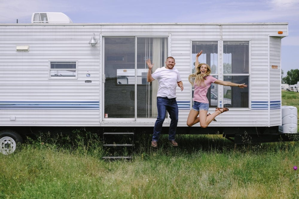 A couple embracing RV life jumping for joy in front of their 2005 park model trailer