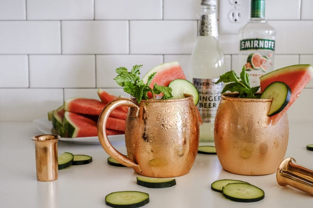 Two copper mugs with cucumber watermelon moscow mule ingredients