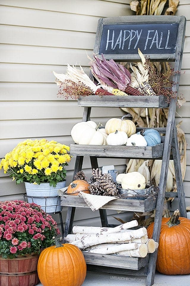 Fall front porch ideas using a tiered wood shelf and pumpkins