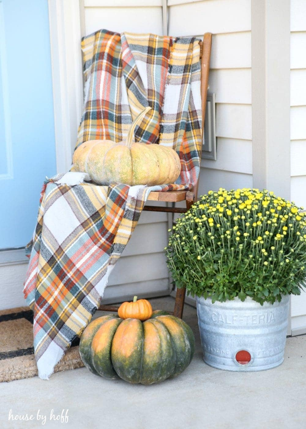 Fall front porch ideas using a plaid scarf draped over a chair with some pumpkins in a corner
