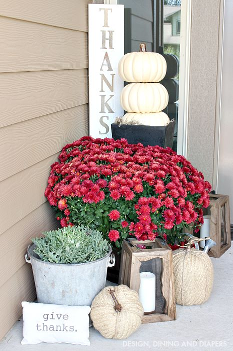 Fall front porch ideas using red mums, wood lanterns and stacking white pumpkins