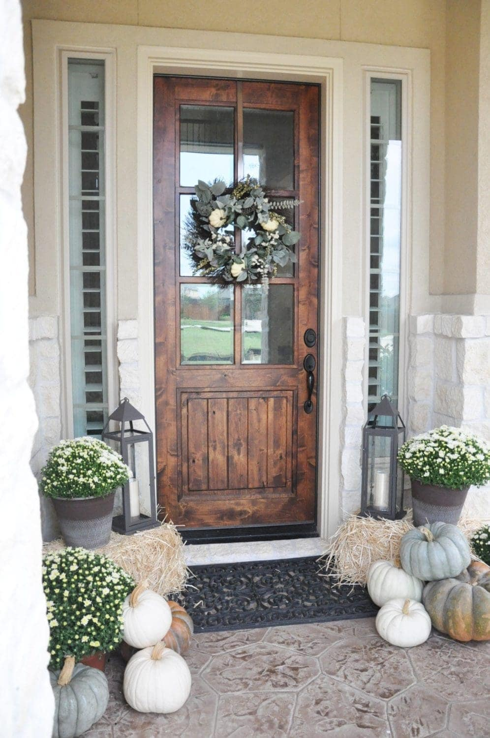 Fall front porch ideas using hay bales, lanterns and neutral colored pumpkins
