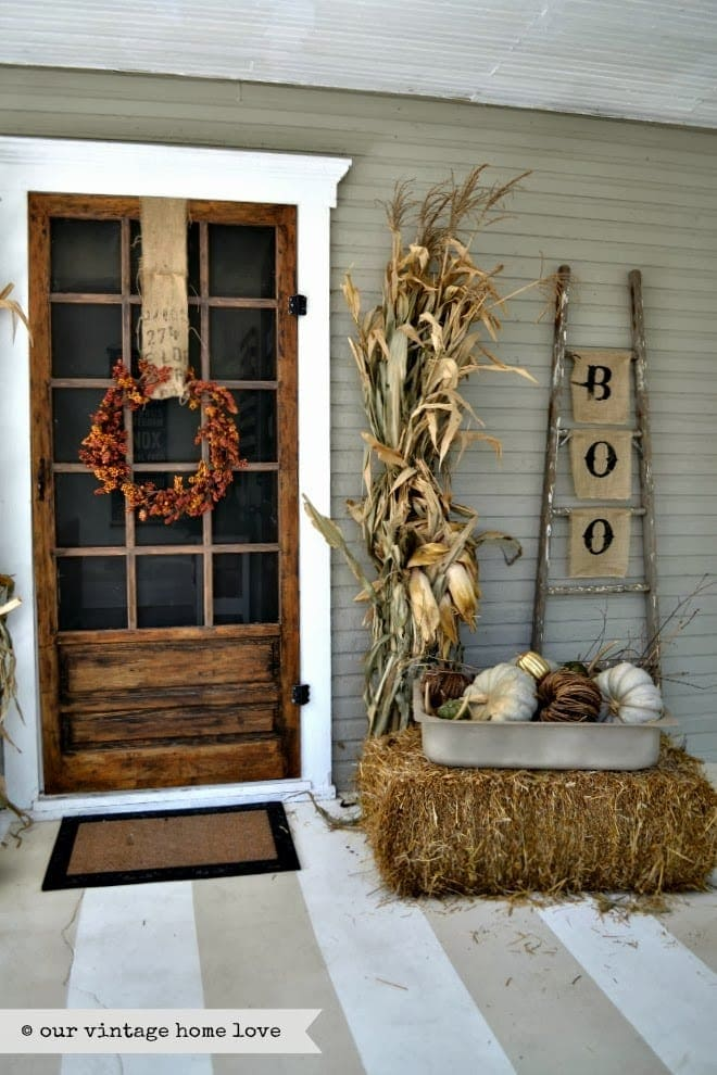 Fall front porch ideas using a hay bale, corn stalks and a rustic blanket ladder with burlap flags that read B-O-O