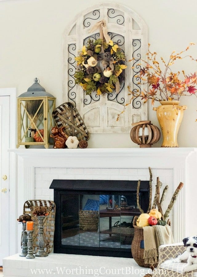 Fall mantel ideas using a basket of sticks, a lantern full of mini pumpkins and a cute fall wreath