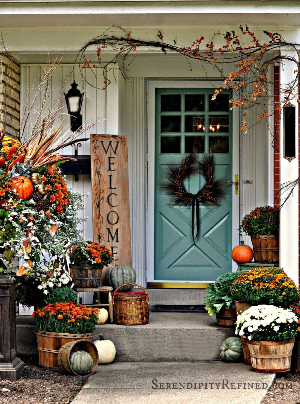 Fall front porch ideas using mums, pumpkins and branches draped over the door